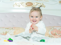 Small caucasian child girl play with toys on the bed at home royalty free stock photo