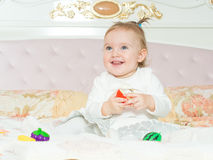Small caucasian child girl play with toys on the bed at home stock photo