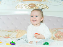 Small caucasian child girl play with toys on the bed at home Stock Images