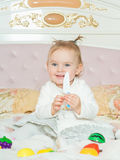 Small caucasian child girl play with toys on the bed at home Royalty Free Stock Photography