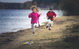Small caucasian children chasing along the beach at the lake, autumn stock photos