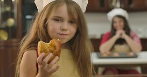 Small Caucasian daughetr looking back at her mom,. turning to camera and chewing sweet baked cookie. Little cute girl stock footage