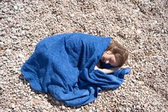 Small caucasian girl lying on beach wraping blue towel in hot summer noon day Stock Photos