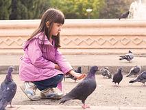 Small caucasian girl and pigeons Royalty Free Stock Photos