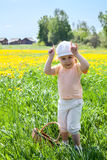Small Caucasian girl playing on meadow in cow Stock Photos