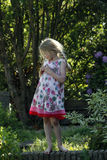 Small caucasian girl wearing summer dress in garden Royalty Free Stock Photography