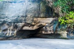 A small cave in the rock above the sandy beach stock photography