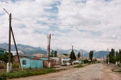 Small Central Asian town with one floor buildings and the mountains background stock photos
