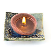 Small ceramic earthenware plate with a candle Royalty Free Stock Photos