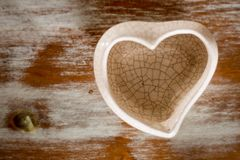 small ceramic vase in heart shape with white and brown background stock photography