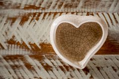 Small ceramic vase in heart shape with white and brown background stock images