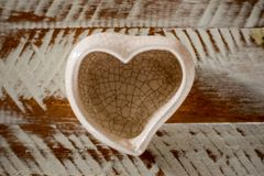 small ceramic vase in heart shape with white and brown background stock photos