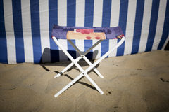 Small chair. Small textile chair on the sand at the beach Stock Image