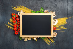 Small chalk board and ingredients for cooking Italian pasta Royalty Free Stock Photo