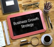 Small Chalkboard with Business Growth Strategy. 3d. Business Growth Strategy - Red Small Chalkboard with Hand Drawn Text and Stationery on Office Desk. Top View Stock Image