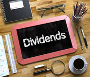 Small Chalkboard with Dividends. 3D. Dividends Handwritten on Small Chalkboard. Dividends Handwritten on Red Small Chalkboard. Top View of Wooden Office Desk royalty free stock image