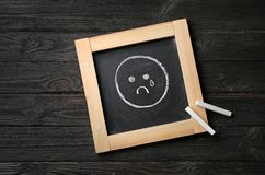 Small chalkboard with drawing of sad crying face on wooden background, top view. Depression symptoms royalty free stock photography