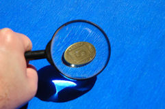 Small change. Coin under magnifier Royalty Free Stock Photography