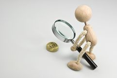Small change. Wooden doll looking on a Cent-Coin trough a magnifier glass Royalty Free Stock Image