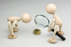 Small change. Two wooden dolls looking at a 50-Pence-coin trough a magnifier Stock Photos
