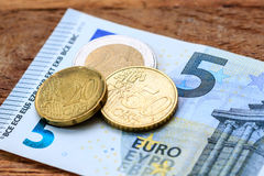 Small change (money). Detail of three coins (20 eurocent, 50 eurocent and 2 euro) on a 5 euro banknote Royalty Free Stock Photography