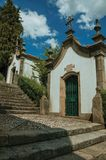 Small chapel in baroque style next to stone staircase. Small chapel finery decorated in baroque style next to stone staircase with green bushes, in a sunny day royalty free stock photography