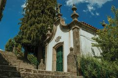 Small chapel in baroque style next to stone staircase. Small chapel finery decorated in baroque style next to stone staircase with green bushes, in a sunny day royalty free stock image