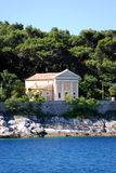 Small chapel in Mali Losinj,Croatia. Seaside vew at small chapel in Mali Losinj at Cikat bay with the pine forest in background Stock Images