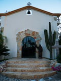 Small chapel recently renovated in Cabo Mexico. Small chapel recently renovated in San Jose del Cabo Baja Mexico. Glass door, cactus and a small bell Stock Image
