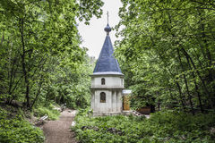 A small chapel in the woods. A small chapel in the dense forest in the distance from the cities Royalty Free Stock Photo