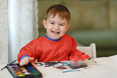 Small charming baby boy in a red robe draws colored paint sitting at the table and smiling at home royalty free stock photos