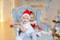 Small charming baby boy in red Santa hats and the little blond g Royalty Free Stock Images