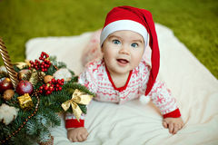 Small charming baby boy in red Santa hats and pajamas with snowf Royalty Free Stock Photo
