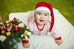 Small charming baby boy in red Santa hats and pajamas with snowf Royalty Free Stock Photo