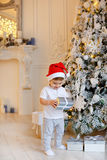 Small charming baby boy in Santa hat and light-colored clothing royalty free stock images