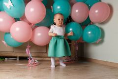 A small, charming child, a girl, celebrates her first birthday, sitting next to her with balloons. Children`s Party Organization. stock photos