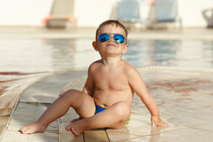 Small charming chubby baby boy in glasses sitting on a pool back Royalty Free Stock Photo