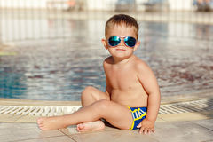 Small charming chubby baby boy in glasses sitting on a pool back Stock Photography