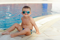 Small charming chubby baby boy in glasses sitting on a pool back Royalty Free Stock Images