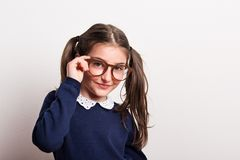 A small cheeky schoolgirl with glasses and uniform in a studio. Royalty Free Stock Photo
