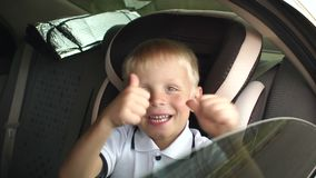 A small cheerful boy sits in a brown child car seat and shows his thumb up. Cute kid is playing and having fun in the kids car seat during the summer journey stock footage