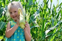 A small, cheerful girl among high, green corn Royalty Free Stock Image