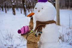 A small cheerful girl holds a big carrot, the nose of a big snowman. A cute little girl has fun in winter park, wintertime Stock Photography