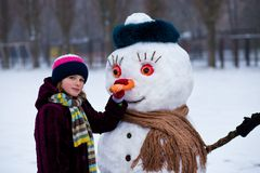 A small cheerful girl holds a big carrot, the nose of a big snowman. A cute little girl has fun in winter park, wintertime Stock Image