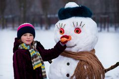 A small cheerful girl holds a big carrot, the nose of a big snowman. A cute little girl has fun in winter park, wintertime Royalty Free Stock Photos