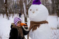 A small cheerful girl holds a big carrot, the nose of a big snowman. A cute little girl has fun in winter park, wintertime Royalty Free Stock Image