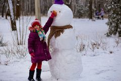 A small cheerful girl holds a big carrot, the nose of a big snowman. A cute little girl has fun in winter park, wintertime Stock Photos