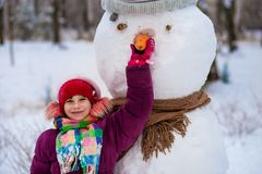 A small cheerful girl holds a big carrot, the nose of a big snowman. A cute little girl has fun in winter park, wintertime Royalty Free Stock Images