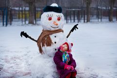 Small cheerful girl near big funny snowman. Cute little girl has fun in winter park royalty free stock photography