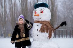 Small cheerful girl near big funny snowman. Cute little girl has fun in winter park royalty free stock image